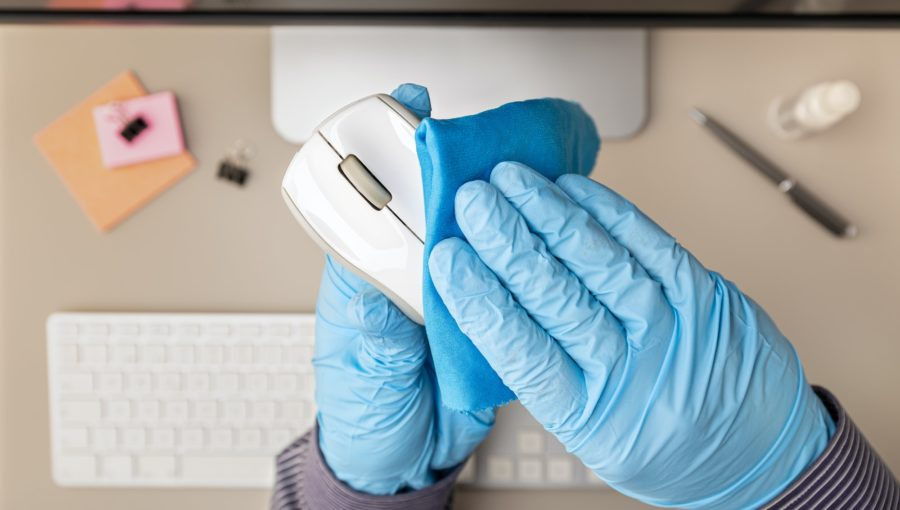 Hand with protective glove cleaning a computer mouse with disinfectant